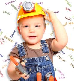 ein Kleinkind in Latzhose und gelbem Helm hält Spielzeugwerkzeug in der Hand, im Hintergrund stehen verschiedene Vornamen
