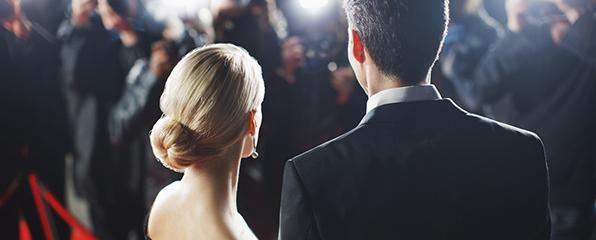 eine Frau und ein Mann in Abendgaderobe stehen auf dem roten Teppich und werden fotografiert