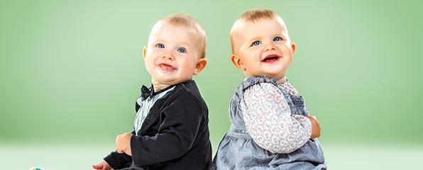 ein Baby im Anzug und Fliege und ein Baby in einem blauen Kleid lachen fröhlich