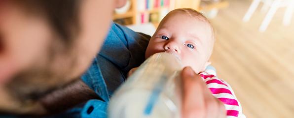 ein Mann hält ein Baby auf dem Arm und füttert es mit einer Flasche
